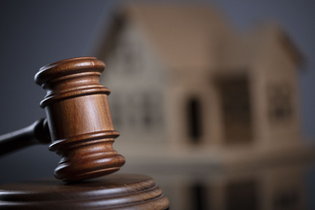 Construction law concept. Wooden gavel on the gray background with the house model.