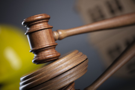 Construction law concept. Wooden gavel on the gray background with the house model and the yellow hardhat. Stock Photo