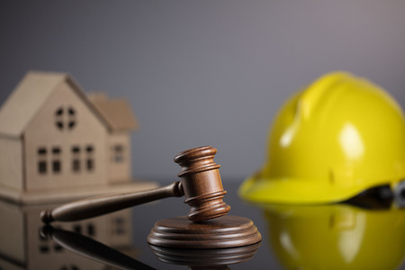 Construction law concept. Wooden gavel on the gray background with the house model and the yellow hardhat. Archivio Fotografico