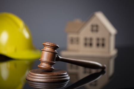 Construction law concept. Wooden gavel on the gray background with the house model and the yellow hardhat. 写真素材