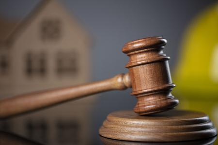 Baurechtliches Konzept. Hölzerner Hammer auf grauem Hintergrund mit dem Hausmodell und dem gelben Bauarbeiterhelm.