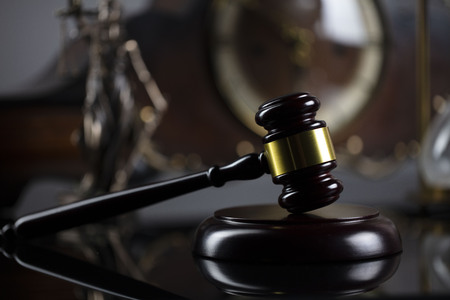 The law concept background. Gavel of the judge and Themis statue on the gray background.