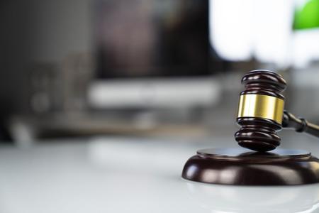 Oficina del abogado. Martillo, escala y computadora en la mesa blanca.