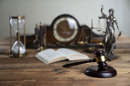 Law concept. Judges gavel on rustic wooden table. Stock Photo
