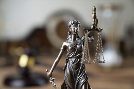 Gesetzessymbole – Themis und Richterhammer auf dem rustikalen Holztisch. Standard-Bild