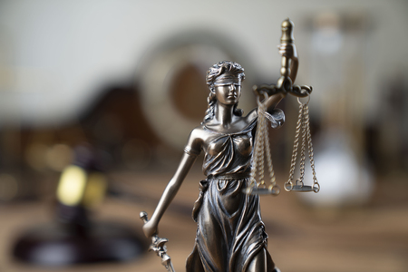 Law symbols – Themis and judge's gavel on the rustic wooden table. Stock Photo