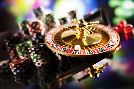 Gambling theme.  Roulette wheel and poker chips on color bokeh background. 免版税图像