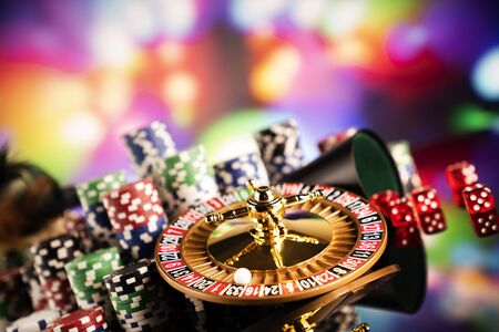 Gambling theme.  Roulette wheel and poker chips on color bokeh background. 写真素材