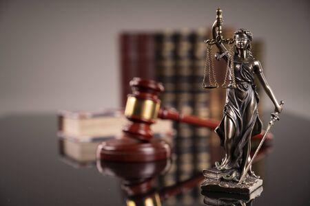 Statua sprawiedliwości - Temida, kodeksy prawne i młotek sędziego.