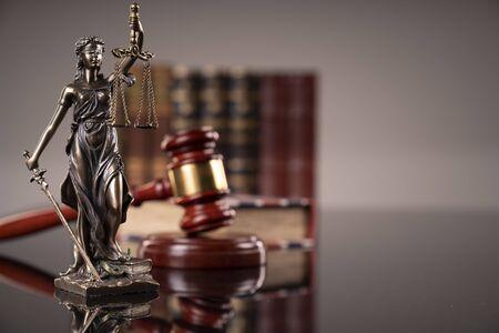 Statua sprawiedliwości - Temida, kodeksy prawne i młotek sędziego. Zdjęcie Seryjne