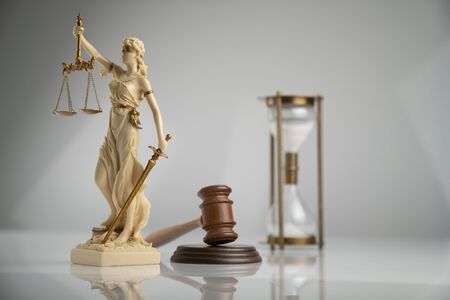 Gavel, hourglass and Themis - statue of justice on white background. Stock Photo