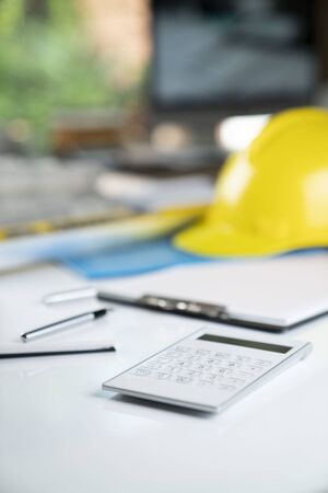Contractor concept. Yellow hard hat and plans on the white table. Stock fotó