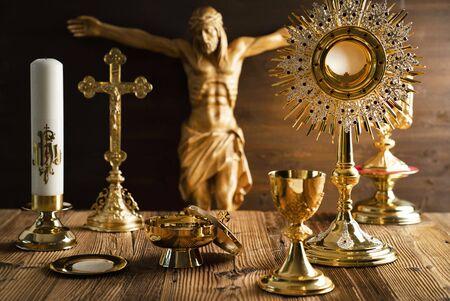 Katholieke concept achtergrond. Het kruis, Jezusfiguur, monstrans en gouden kelk op het altaar.