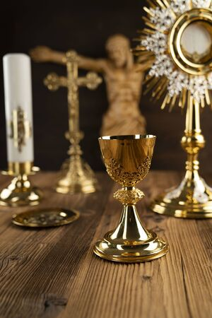 Catholic concept background. The Cross, Jesus figure, monstrance and golden chalice on the altar.