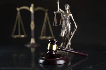 Law and justice theme.  Gavel of  the judge, Themis statue and the scale on the dark background.7