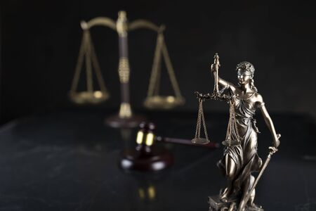 Law and justice theme.  Gavel of  the judge, Themis statue and the scale on the dark background.