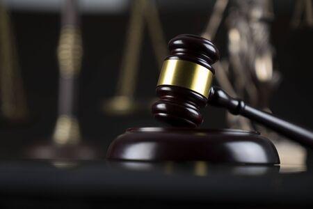 Temat prawa i sprawiedliwości. Młotek sędziego, posąg Temidy i waga na ciemnym tle. Zdjęcie Seryjne