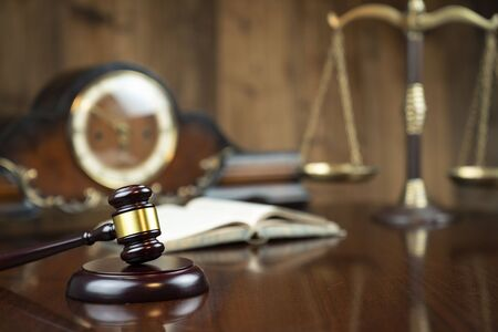 Law concept. Gavel of  the judge, the legal code, the clock and the scale on the wooden background.