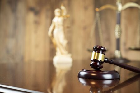 Law concept. Gavel of  the judge, Themis statue and the scale on the wooden background.