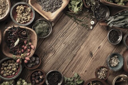 Spices theme. Collection of spices in bowls on wooden rustic table. Place for text or typography.