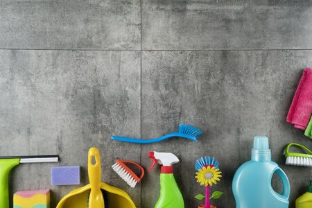 Colorful cleaning products on gray tiles. Top view. Place for logo or text.