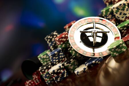 Casino-Thema. Glücksspiele. Roulette, Würfel und Pokerchips auf einem bunten Bokeh-Hintergrund.