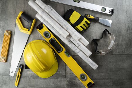 Contractor theme. Rolls with building projects, tools, crash helmet and spirit level on stone background.