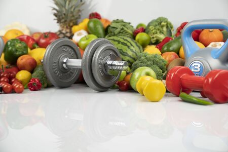 Fitness concept – healthy nutrition and equipment for fitness exercises on the white background.