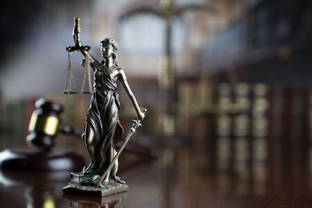 Law theme. Themis statue, judge gavel and scale of justice in the law faculty library. Banco de Imagens