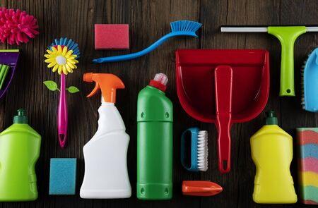 Autumn house cleaning theme.  Colorful cleaning products on rustic wooden table. Top view shot. Place for typography.
