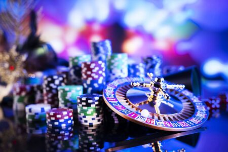 Casino theme. Gambling games. Roulette and poker chips on a colorful bokeh background.