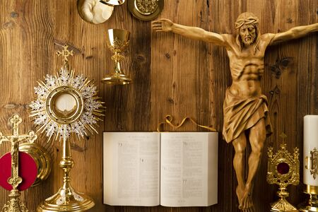 Catholic religion symbols. The Cross, monstrance, Jesus figure, Holy Bible and golden chalice on the rustic wooden table. Stockfoto