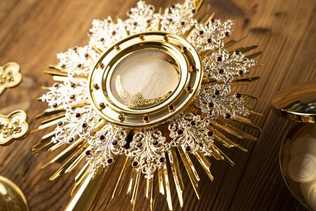 Catholic religion symbols. The Cross, monstrance, Holy Bible and golden chalice on the rustic wooden table.