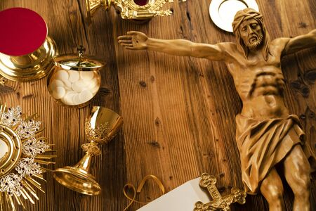 Catholic religion symbols. The Cross, monstrance, Jesus figure, Holy Bible and golden chalice on the rustic wooden table.
