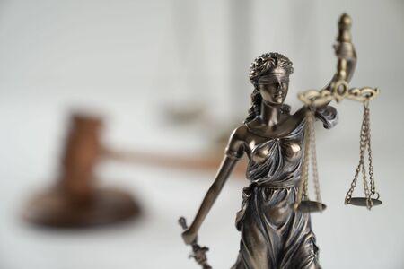 Kompozycja symbolu prawa. Młotek sędziego, posąg Temidy i waga sprawiedliwości na złamanym białym tle.