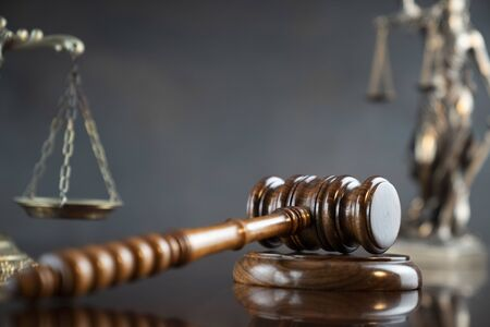Tema de la ley. Martillo del juez, estatua de Themis y escala de la justicia sobre fondo gris.