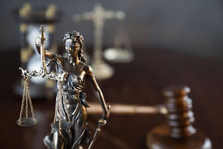 Law theme. Gavel of the judge, Themis statue and scale of justice on gray background.