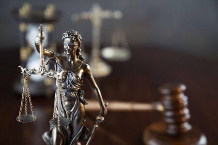 Thema Recht. Hammer des Richters, Themis-Statue und Gerechtigkeitsskala auf grauem Hintergrund.