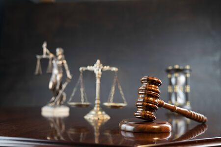 Law theme. Gavel of the judge, Themis statue and scale of justice on gray background. Stock Photo