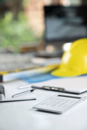 Architecture and construction concept. Empty notebook, rolls with building projects, spirit level  and architect yellow helmet on tabletop. Stockfoto