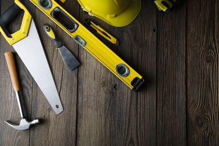 Contractor concept. Tools of the contractor : yellow hardhat, libella and hand saw on the rustic wooden background.