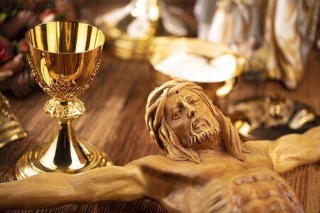 Symbole religii katolickiej. Krzyż, monstrancja, figura Jezusa, Pismo Święte i złoty kielich na rustykalnym drewnianym stole. Zdjęcie Seryjne