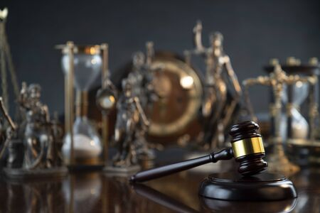 Law and justice theme. Judge's gavel, Themis  statue, scale, hourglass and old clock on the shining wooden brown table and the gray background.