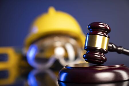 Construction law. Helmet and gavel on the blue background.