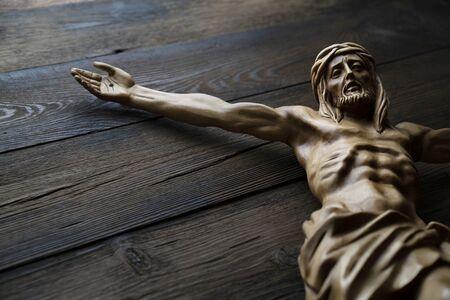 Cruciefied Jesus figure isolated on rustic dark brown table.