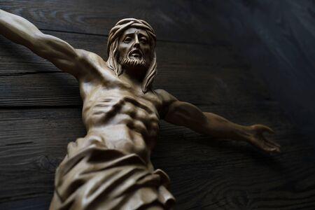 Figura Jezusa Ukrzyżowanego na białym tle na rustykalnym ciemnobrązowym stole.
