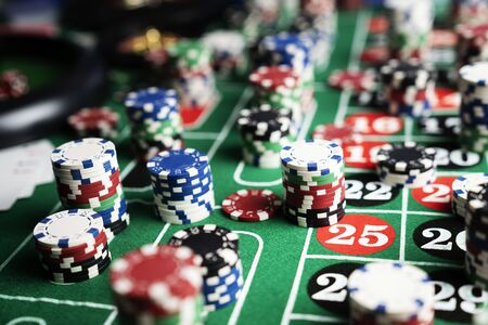 Casino felt green table with red and black numbers. Stack of poker chips.
