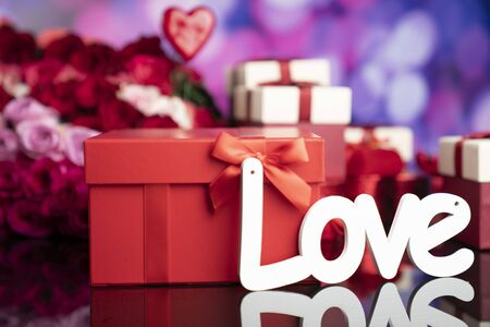 Valentines day concept. Gifts in boxes, red hearts and big bouquet of natural roses on blue bokeh background.