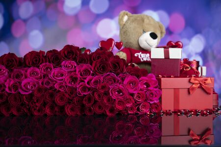 Valentines day. Teddy bear, gifts in boxes, red hearts and big bouquet of natural roses on blue bokeh background. Standard-Bild
