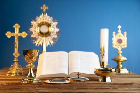 Catholic religion concept. Catholic symbols composition. The Cross, monstrance,  Holy Bible and golden chalice on the altar. Blue background.